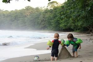 Bilden visar två barn som bygger sandslott på en tropisk strand.