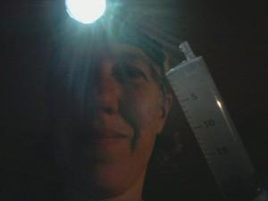 Bilden visar en person med pannlampa och en spruta med sockerlösning i.